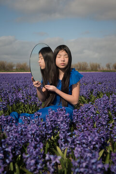 Girl in blue dress sitting  with round mirror in field of purple flowers