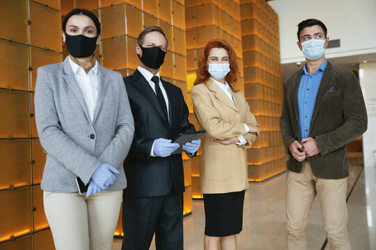 Four elegant coworkers following the safety precautions