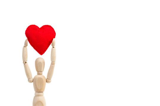 Maniqui de madera articulado sosteniendo entre sus manos un corazón rojo sobre un fondo blanco liso y aislado. Vista de frente. Copy space.