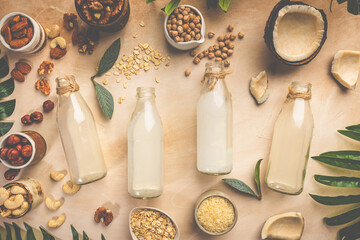 Fototapeta Vegan non dairy plant based milk in bottles and ingredients on light background. Lactose free milk substitute. Top view. obraz