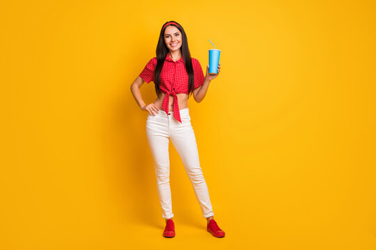 Full length photo of pretty cute young girl dressed red shirt holding blue soda glass isolated yellow color background