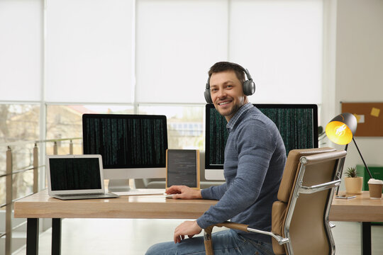Happy programmer with headphones working at desk in office