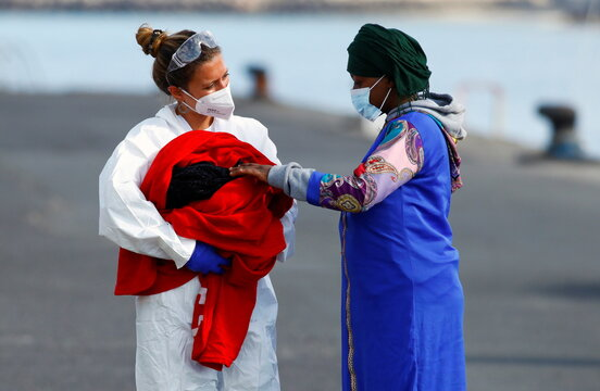 Nurse holds a newborn baby next to her mother, in the port of Arguineguin