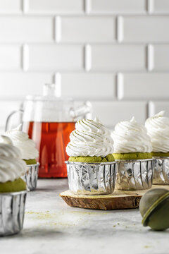 Matcha cupcakes with meringue frosting with tea on white background
