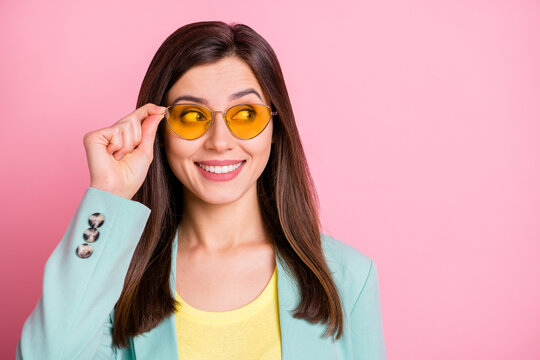 Photo of attractive charming young woman wear sunglass look empty space smile isolated on pink color background