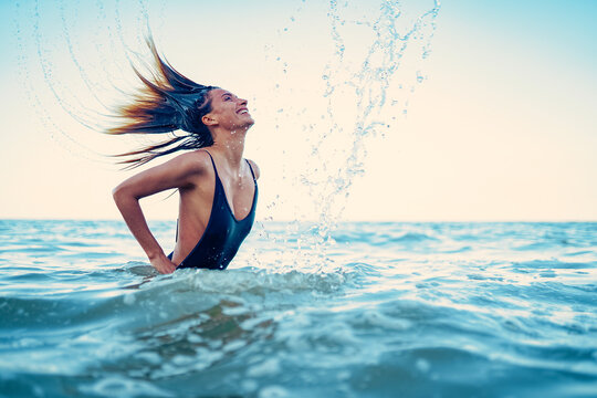 Beauty Model Girl Splashing Water with her Hair. A young woman i