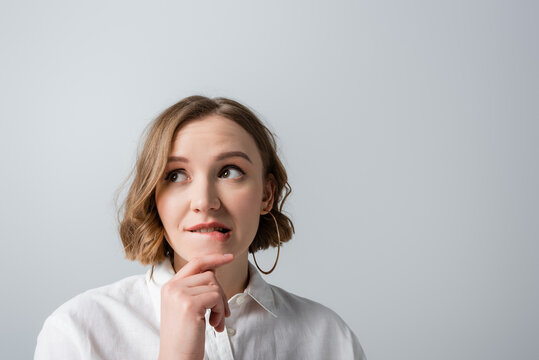 pensive overweight woman in white shirt biting lips isolated on grey