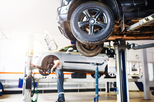 The car is lifted for repair on a lift in a car service station, a mechanic in overalls repairs in the background. Wheel close-up, tire service