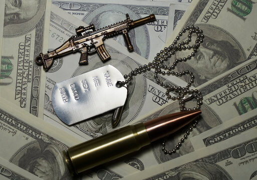 The medallion of a military soldier lies on dollar bills. Concept: price of a military operation, military mercenaries, army pension for the military.