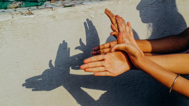 Pair of hands creating shadow puppet in sunshine