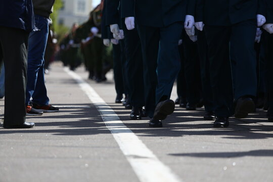 a solemn parade in the city square during a military holiday, the best soldiers marching synchronously in a column of systems, stamping step with weapons in hand, demonstration of military power
