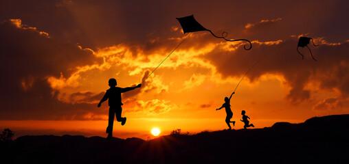 Fototapeta Sylwetki dzieci puszczających latawca o zachodzie słońca obraz