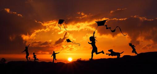 Fototapeta Sylwetki dzieci puszczających latawce o zachodzie słońca obraz