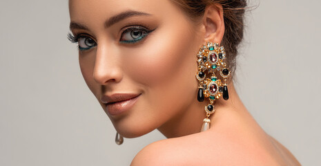 Beautiful woman with long big earrings. Beauty girl with elegant hairstyle and evening make-up....