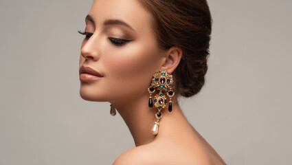 Obraz Beautiful woman with long big earrings. Beauty girl with elegant hairstyle and evening make-up. Makeup, cosmetics and jewelry - fototapety do salonu
