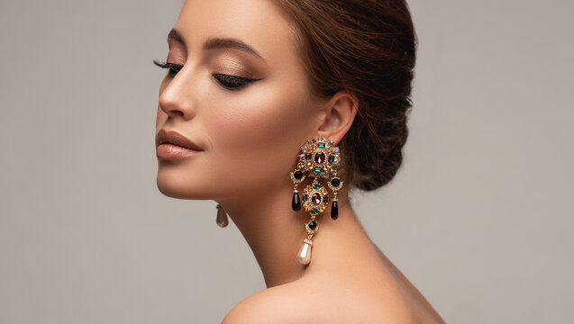 Beautiful woman with long big earrings. Beauty girl with elegant hairstyle and evening make-up. Makeup, cosmetics and jewelry