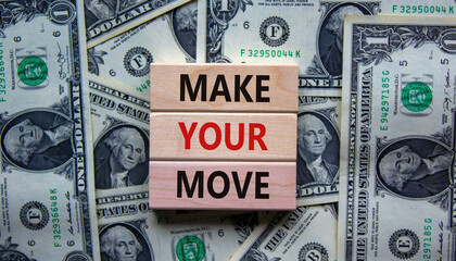 Make your move symbol. Wooden blocks with words 'Make your move'. Beautiful background from dollar bills. Business, make your move concept, copy space.