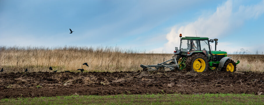 BAYKIVTSI, TERNOPIL REGION, UKRAINE - APRIL 20, 2021: a tractor 90s John Deere 2850 with a homemade plow prepares the field for sowing, panoramic view