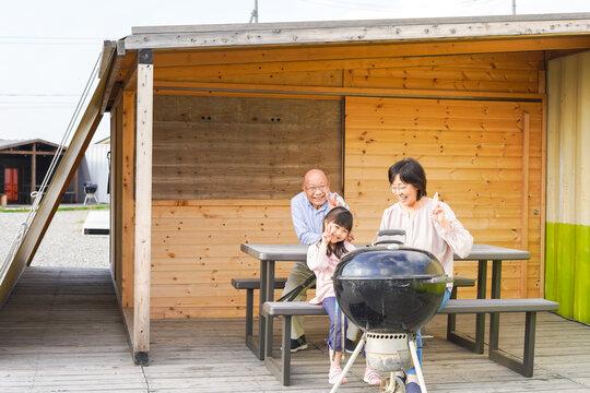 孫とキャンプをする高齢の夫婦