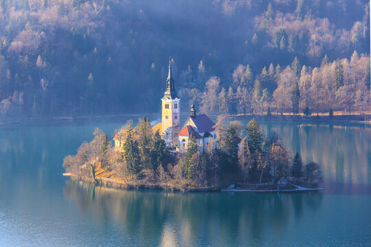 Church of the Assumption of Mary on Lake Bled in the haze of a sunny January morning.