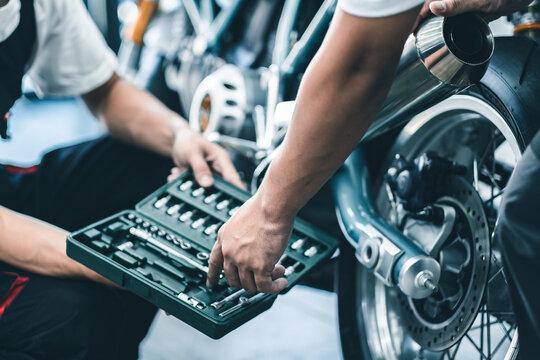 Bike repair. Young man repairing  motobike in garage.mechanic fixing motocycle engine.Serious young man repairing his motorcycle in bike repair shop.