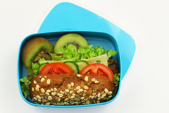 Whole grain oat roll with cheese, lettuce, cucumber, tomato and kiwi fruit in blue lunchbox on white background