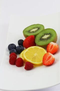 Best source of Vitamin C: strawberries, bluberries, raspberries, kiwi fruit and lemon on white plate