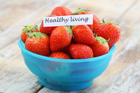 Healthy living note with sweet strawberries in blue bowl