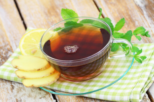Organic tea in transparent cup, fresh mint leaves, slices of lemon and fresh ginger on rustic wooden surface