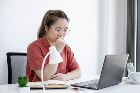 A business woman thinks about work in her office, working from home to prevent the spread of COVID-19, she is having a serious meeting with a partner. The idea of working from home.
