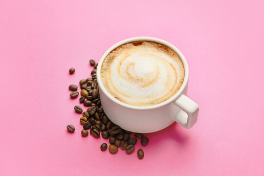 Cup of hot cappuccino on color background