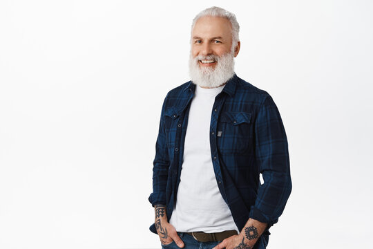 Stylish old man with beard and tattoos, standing relaxed with hands in pockets, looking aside at logo banner with pleased smile, standing over white background