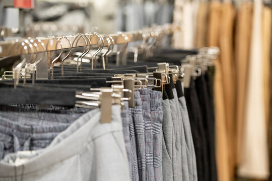Variety of new trendy casual clothes hanging in row on rack