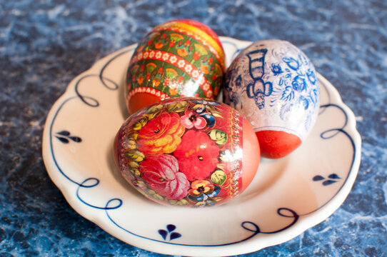 Easter. Three Easter eggs with transparent film with drawings on a white plate.