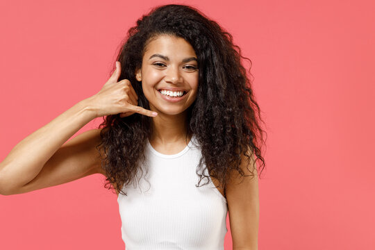 Young smiling fun happy cheerful friendly african american woman 20s wear casual white tank shirt doing phone gesture like says call me back isolated on pink color background People lifestyle concept