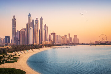 Sunset view of the Dubai Marina and JBR area and the famous Ferris Wheel and golden sand beaches in...