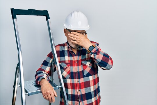 Handsome mature handyman close to construction stairs wearing hardhat covering eyes with hand, looking serious and sad. sightless, hiding and rejection concept