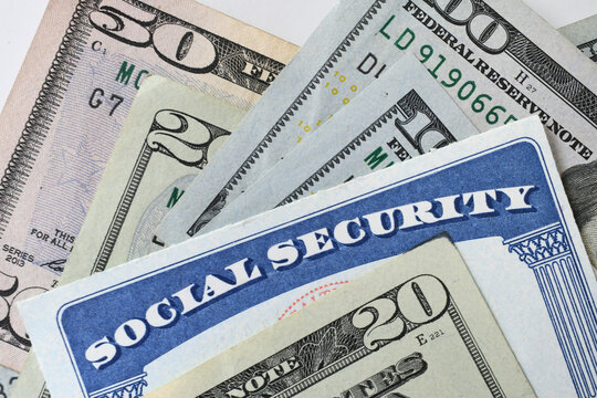 Social Security Card with cash money dollar bills - living on a fixed income, benefits SSN. Every American is issued a social security number on a legal document, your social security card.