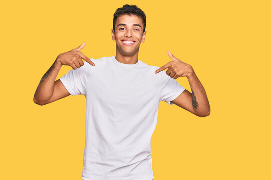 Young handsome african american man wearing casual white tshirt looking confident with smile on face, pointing oneself with fingers proud and happy.