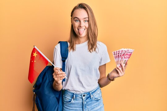 Beautiful blonde woman exchange student holding china flag and yuan banknotes sticking tongue out happy with funny expression.