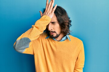 Young hispanic man wearing casual clothes surprised with hand on head for mistake, remember error. forgot, bad memory concept. Wall mural