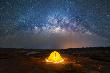 Fototapeta Camping tent under sky on mountain hills with the milky way with bright stars at night in travel on holiday vacation concept. Natural universe space landscape background. Adventure tourist activity.