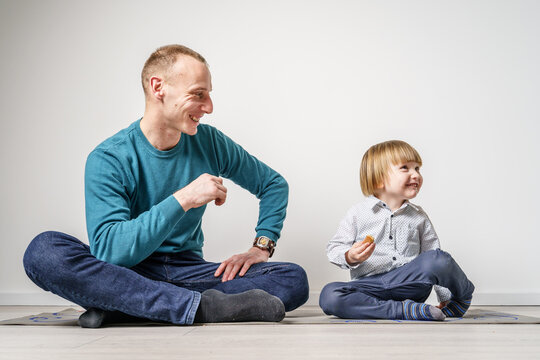 Father and son sitting on the floor in front of white wall looking at each other happy parenthood trust children's growing up and father's day concept real people