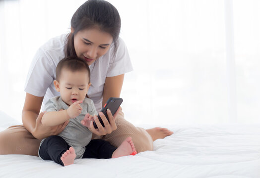Young asian mother and little baby girl or newborn selfie with smart phone on bed in bedroom, happiness mom and daughter using phone video call at home, two people, family and communication concept.