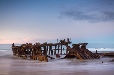 bow section of the ship wreck SS Maheno awash in the surf on the beach