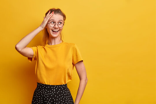 Horizontal shot of pretty joyful woman looks away keeps hand on head smiles broadly wears basic t shirt and skirt optical eyeglasses isolated over yellow background blank space for your advert