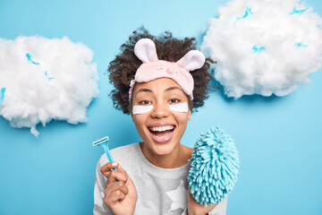 Fototapeta Daily morning hygiene routines concept. Cheerful young Afro American woman in nightwear holds razor and sponge smiles broadly awakes in good mood enjoys nice day domestic atmosphere poses indoor