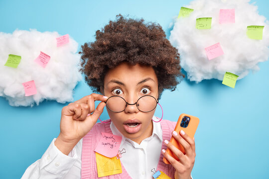 Headshot of startled young female teacher reacts on shocking information keeps hand on rim of spectacles uses modern smartphone for texting writes tasks to do on colorful stickers. Post it notes