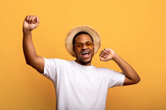 Handsome black man in sunglasses, t-shirt and straw hat raising his hands up, dancing on yellow studio background