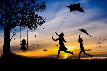 Fototapeta Sylwetki dzieci bawiące się latawcami i na huśtawce obraz